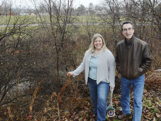 Cathie Rowand | The Journal Gazette Abigail King of Save Maumee Grassroots Organization, with business owner Greg Doublas, shows a type of vegetation that helps water quality along Bullerman Ditch on the city's northeast side.