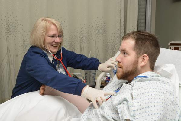 Michelle Davies | The Journal Gazette Jan Trahin, an LPN in the burn unit at St. Joseph Hospital since it opened, checks the pulse of her patient Andrew Heath, from Ligionier, who has a work-related contact burn.