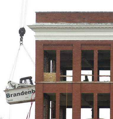 An excavator is lowered along the side of a GE building as the structure is slowly dismantled from the inside out.
