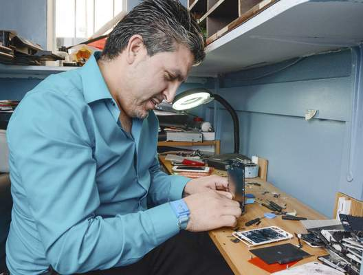 Michelle Davies | The Journal Gazette Cesar Ruiz, 31, owner of Wayne PC Tech and vice president of the Hispanic Chamber, repairs phone screens Monday in his shop on South Calhoun Street.