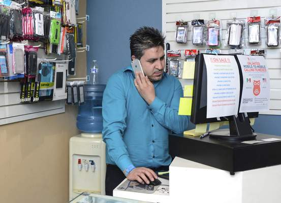 Michelle Davies | The Journal Gazette Cesar Ruiz, owner of Wayne PC Tech, talks to a customer about her broken phone screen while in his shop on South Calhoun Street Monday afternoon.