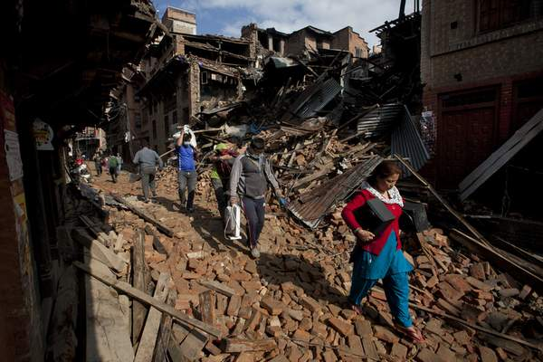Associated Press People carry belongings from their destroyed homes through debris of Saturday's earthquake Monday on the outskirts of Kathmandu.