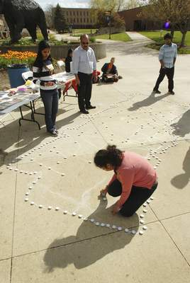 Samuel Hoffman | The Journal Gazette IPFW graduate student Kumjd Joshi sets out a line of candles in the shape Nepal for a vigil for victims of the deadly earthquake at IPFW, Thursday.
