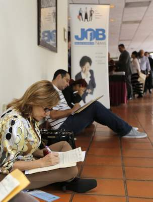 In this Oct. 22, 2014 photo, job seekers fill out job applications at a job fair in Miami Lakes, Fla. The Labor Department releases employment data for November on Friday, Dec. 5, 2014. (AP Photo/Alan Diaz)