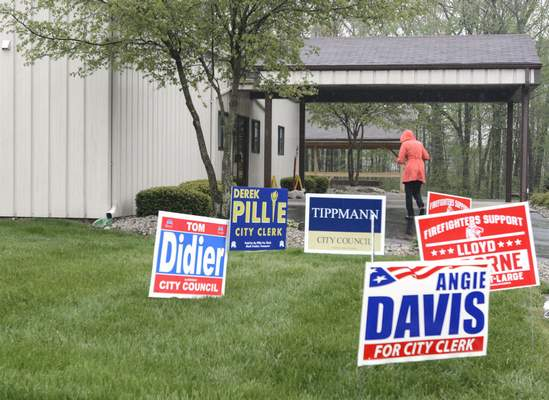Michelle Davies | The Journal GazetteProtected against the rain voter goes into Northridge Baptist Church on Cook Road Tuesday morning.