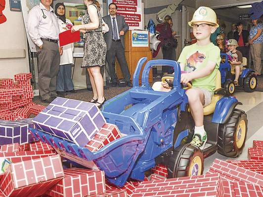 Michelle Davies   The Journal Gazette Quint Lawrence, 5, a patient at Lutheran Children Hospital, participates in the symbolic groundbreaking for the hospital's expansion Thursday by moving cardboard bricks.