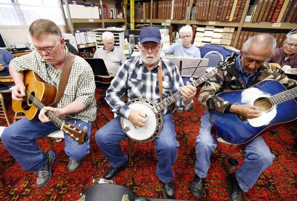 Photos by Chad Ryan | The Journal Gazette Stanley Sallee, left, on the guitar, Lenial Townsend, center, picking his banjo, and Clifford Sloan, also playing guitar, sit in on a Bluegrass Jam group session at the Old Jail Museum in Warsaw.