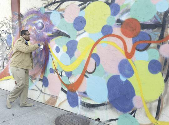 Local artist Theoplis Smith III paints a mural on the side of Wunderkammer Company, 3402 Fairfield Ave, Wednesday. Smith was taking advantage of Wednesday's sunny and warmer weather to finish his artwork.