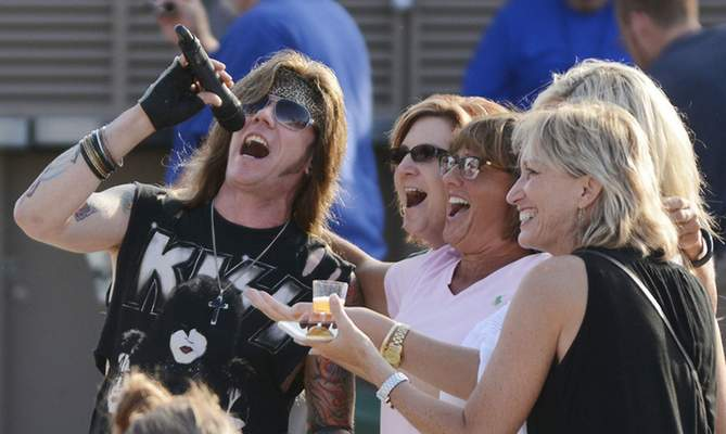 """Drew Wireman, lead singer of the band Cougar Hunter, sings the Journey song """"Don't Stop Believin'"""" with women from the crowd at Parkview Field."""