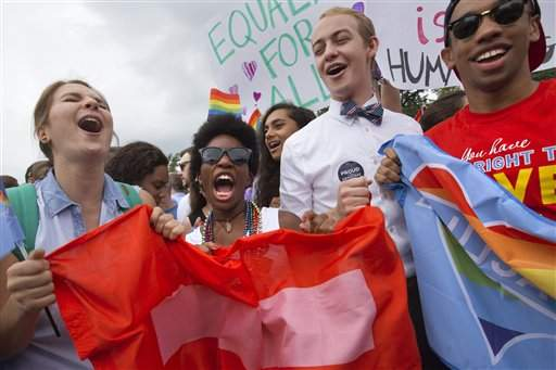 From left, Annie Katz of the University of Michigan, Zaria Cummings of Michigan State University, Spencer Perry of Berkeley, Calif., and Justin Maffett of Dartmouth University, celebrate outside of the Supreme Court in Washington, Friday June 26, 2015, after the court declared that same-sex couples have a right to marry anywhere in the US.   (AP Photo/Jacquelyn Martin)
