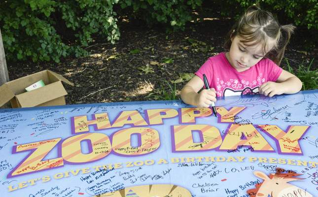 Michelle Davies | The Journal Gazette Addison Smith, 4, of Fort Wayne, takes a moment to sign birthday card for the Fort Wayne Children's Zoo's 5oth birthday celebration Wednesday afternoon.