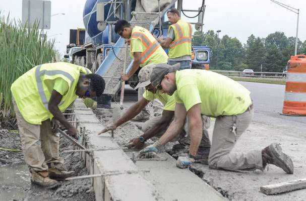 Michelle Davies   The Journal Gazette Thursday morning on Coliseum Boulevard, Chris Roberts, a Construction Trades instruction with Anthis' Summer Program of Construction Trades, front right, floats the concrete on a curb repair along with his students, left, Kevin Salter, 18, a recent grad of Carroll High School, Michael Wright, kneeling right, a supervisor with Ivy Tech's construction management program, standing left, Alejandro Lugo, 17, a student at South Side High School, and Rob Gerkin, standing right, a driver / trainer for Erie Haven.