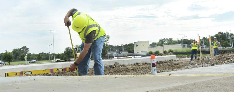 Cathie Rowand | The Journal Gazette Sub contractors Crosby Excavating and Wayne Asphalt & Construction Co., Inc. do site work in preparation for new chapel construction at Bishop Dwenger High School Thursday.