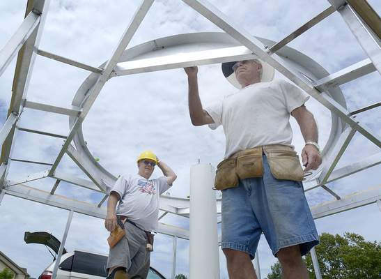 Pinckney, left, and Lauinger attach the base ring during construction of the mini-observatory. The observatory will house the department's new 8-inch mirror telescope in a mount designed and built by an IPFW student.