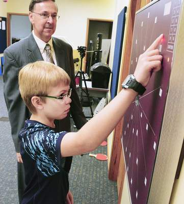 Cathie Rowand | The Journal Gazette Dr. Carl Myers works with Austin Bedwell, 11, on peripheral awareness, hand-eye coordination and reaction time Thursday at the Indiana Vision Development Center. August is National Children's Vision and Learning Month. Many children do not know they have a vision problem because they assume the way they see is the way everyone sees.
