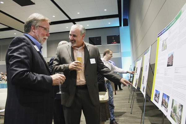 Rachel Von | The Journal Gazette Mark Becker, left, and Don Osika check out the projects included in a state grant proposal during a presentation and celebration Tuesday for the Regional Cities Initiative at the Parkview Mirro Center for Research and Innovation.