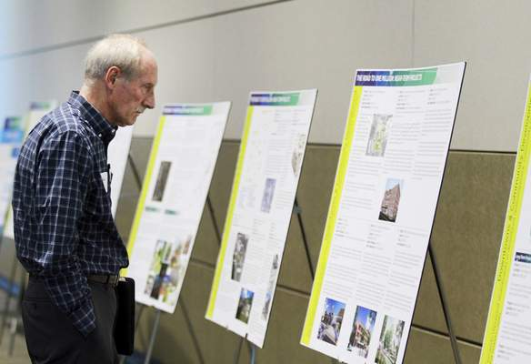 Rachel Von | The Journal Gazette John Stafford checks out the projects that are included in the proposal during a presentation and celebration for the Regional Cities Initiative at the Mirro Center for Research and Innovation, 10622 Parkview Plaza Dr, Fort Wayne, IN on Tuesday. GALLERY