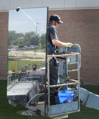 Samuel Hoffman | The Journal Gazette O'Neil's Glass employees Damon Sinninger, left, holding glass from behind, and Jason Hatfield prepare to replace a cracked pane at the Rhinehart Music Center at IPFW on Tuesday.