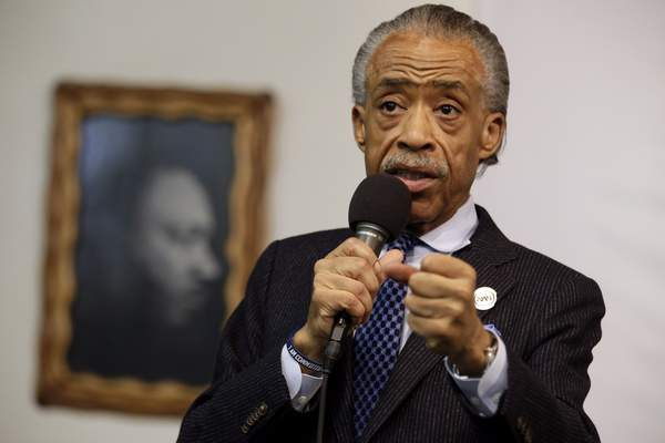 Associated Press – FILE - In this May 2, 2015 file photo, a portrait of the Rev. Dr. Martin Luther King Jr. hangs on the wall behind the Rev. Al Sharpton as he speaks during a rally at the National Action Network, in New York.