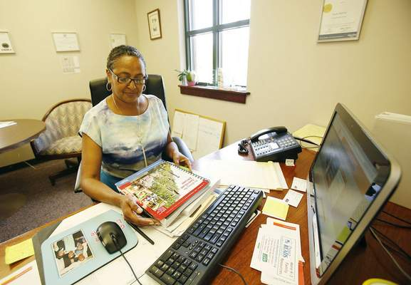 Chad Ryan | The Journal Gazette Paula McGee, director of development and program research for the Urban League, keeps numerous books and forms in her office that she shows to first-time home buyers to help them understand loan details and home ownership responsibilities.