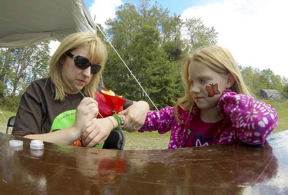 Rachel Von | The Journal Gazette Barb Bradtmiller, left, gives Kyleigh Hale, 7, a wrist art design during the Monarch Festival at the Eagle Marsh Nature Preserve on Sunday. Visitors were able to view live monarch caterpillars and adults as well as learn about butterflies, plant a milkweed, make a butterfly costume and much more! VIDEO / GALLERY