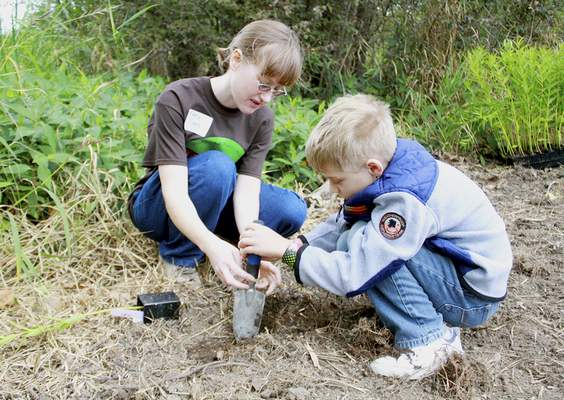 Rachel Von | The Journal Gazette Liam Bredneyer, 9, right, and Katia Cook work together to plant a milkweed during the Monarch Festival at the Eagle Marsh Nature Preserve on Sunday. Visitors were able to view live monarch caterpillars and adults as well as learn about butterflies, plant a milkweed, make a butterfly costume and much more! VIDEO / GALLERY