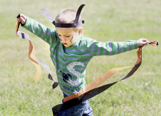 Logan Craig, 3, flaps around with butterfly wings made out of streamers during the Monarch Festival.