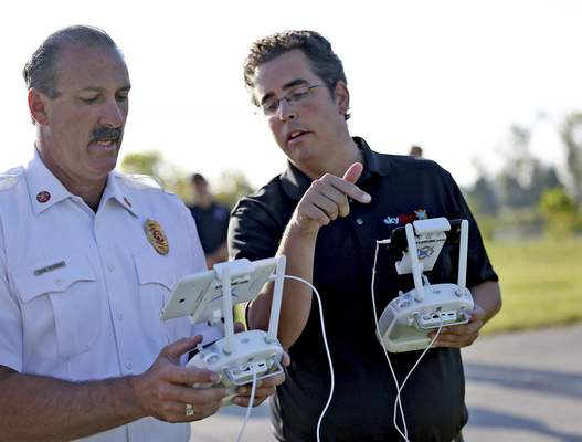 Wayne Township Fire Department Chief Gene Konzen, left, trains with Ben Kroll, with SkyFire Consulting, on drones at the Wayne Township Fire Department Educational Complex, Thursday, Sept. 10, 2015. The department is hoping to use the unmanned aircraft in less picturesque settings, supporting Wayne Township firefighters in all kinds of situations, from hazardous material spills to search-and-rescue operations. (Kelly Wilkinson/The Indianapolis Star via AP) NO SALES; MANDATORY CREDIT