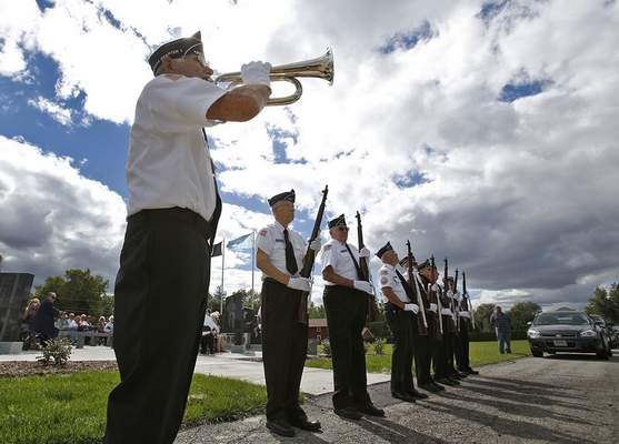 Garry Sink holds a bugle as taps is broadcast through a speaker following a gun salute by other members of the Korean War Veterans Association.