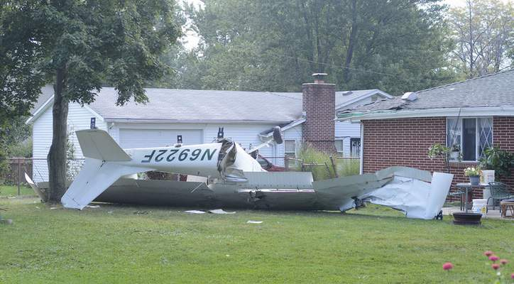 Samuel Hoffman | The Journal Gazette A single-engine plane is in pieces in the backyard of a home at 1414 Ludwig Park Drive early Saturday after it clipped a tree and the house's roof. The crash scene is near Smith Field on the city's north side.