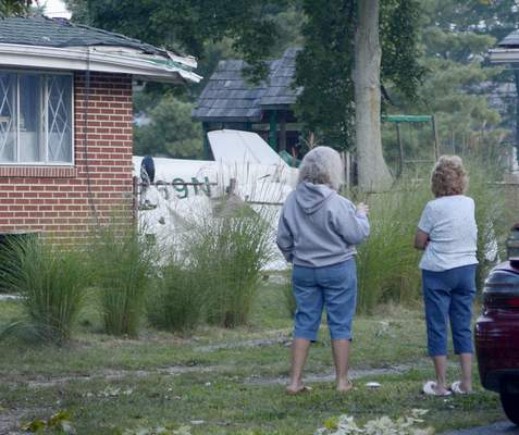 Samuel Hoffman | The Journal Gazette Neighbors talk about the small plane crash at 1414 Ludwig Park Drive early Saturday. The plane clipped trees and the corner of the house and landed upside down.