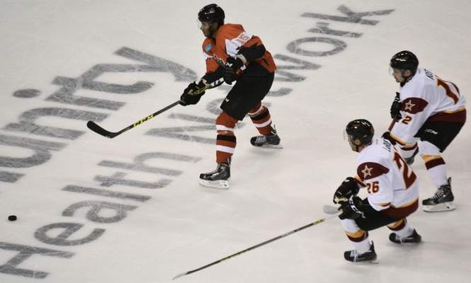 Justin A. Cohn | The Journal Gazette Kyle Thomas of the Komets, left, passes the puck as he's chased by Zack LaRue, bottom, and Branislav Kost of the Indy Fuel in a preseason game Wednesday.