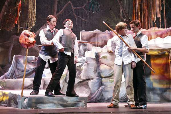 """Photos by Chad Ryan   The Journal Gazette Lucas Lebo, 14, left, playing Henry, pushes a spear against Skyler Neuhaus, 13, playing Sam, while Ben Westropp, 14, playing Jack, holds onto Miles Warshauer, 13, playing Ralph, during rehearsal for the Fort Wayne Youtheatre production of """"Lord of the Flies"""" at Arts United Center."""