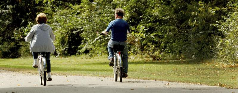 Samuel Hoffman | The Journal Gazette Bicyclists get exercise and improve their health by riding along the Rivergreenway in Foster Park.