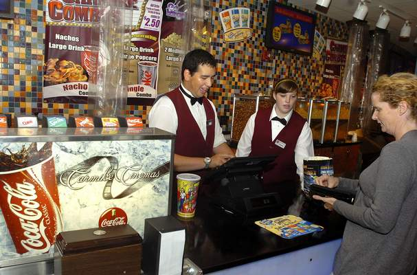 Carmike Cinemas employees Eric Toy (left) and Sarah Arnold (right) help a movie-goer on Saturday evening with refreshments. (For Paul's story)