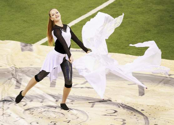 """North Side color guard member Rhiannon Freimuth performs with a flag during the band's performance of """"Time After Time."""""""