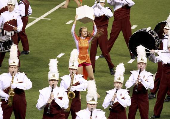 """Color guard member Jordan Stevens dances surrounded by band members during the school's performance of """"The Greatest of These: Hope, Faith, Love."""""""