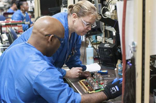 Courtesy Denaryl Mojet and Dawn Hayden check over a circuit board at BAE Systems' facility on Airport Expressway.
