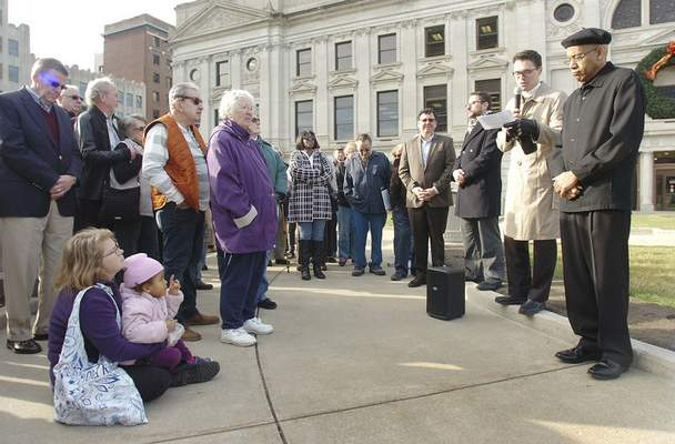 Samuel Hoffman | The Journal Gazette: Kimberly Koczan, left, and her daughter Maya, 4, listen as the Rev. Jeff Lehn, senior pastor of Fort Wayne's First Presbyterian Church, speaks at Friday's interfaith support rally for Muslims on Friday on the Courthouse Green.