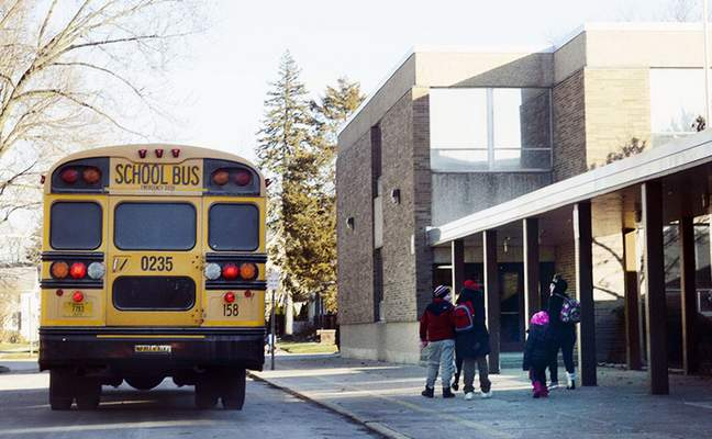 Cathie Rowand | The Journal Gazette FWCS students walk home after a bus drops them off at Nebraska Elementary School at the end of the school day Tuesday afternoon.