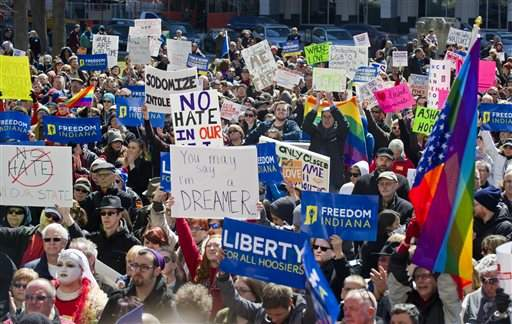 In this March 28, 2015, photo, LGBT activists rally outside the State House in Indianapolis. (AP Photo/Doug McSchooler, File)