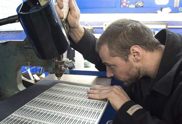 Photos by Michelle Davies   The Journal Gazette Jared Buell lines up a sheet of printed aluminum for holes to be punched. He works at Prentice Products, a full-service screen printing, digital printing and metal-etching company, an investment of the Regional Angel Investment Network.