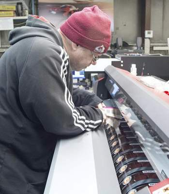 Michelle Davies   The Journal Gazette Jeremy Joslin, digital print department leader at Prentice Products, checks the colors with a Pantone color book on a print run of control panel covers.