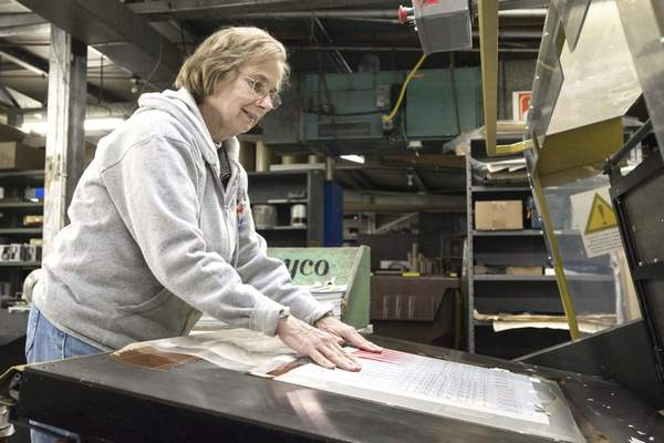 Working at the die-cutting machine at Prentice Products, Susan Reddin places a sheet of plastic rulers on the bed of the machine.