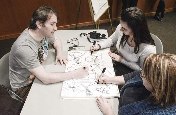 Michelle Davies | The Journal Gazette Artist Frank Louis Allen takes time to draw with with Jaclyn Garver, top right, and Sandra Fouty who attended his lecture Thursday at Ivy Tech Community College Northeast. Allen has been diagnosed with autism and retinitis pigmentosa, a chronic hereditary eye disease that gradually degenerates the retina.