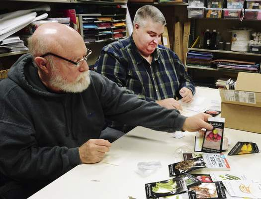 Photos by Cathie Rowand   The Journal Gazette Volunteers Glenn Hile, left, and Chris Knipstein bag seeds for the Little Turtle seed library. Little Turtle Branch is the only library in the area to have started a seed library where people can check out garden seeds for free.
