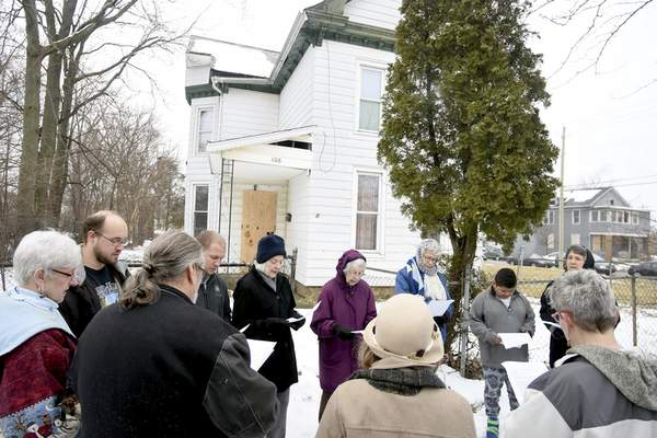 Participants sing and read Scripture during a Heal the Land service on Saturday in front of the house where three men were found slain Feb. 24 on East Lewis Street.