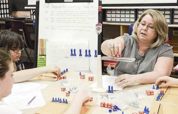 Michelle Davies | The Journal Gazette Teacher Diana Crisler works with Raven Bradford, top left, and Aubree Armstrong during a project last weekat Jeff H. Towles Montessori School.