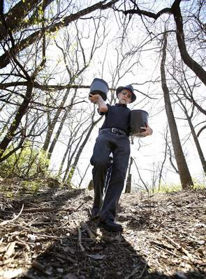 Chad Ryan | The Journal Gazette John Fabini carries conatiners of mulch to put down around new tree plantings as volunteers clean up garbage and plant trees along the bank of the Maumee River east of the Anthony Blvd. bridge on Sunday as part of Save Maumee's Earth Day project.