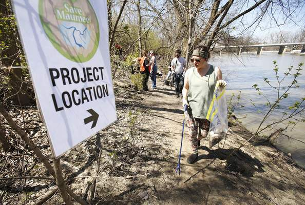 Chad Ryan | The Journal Gazette Nicole Harris looks for trash as she and other volunteers clean up garbage and plant trees along the bank of the Maumee River east of the Anthony Blvd. bridge on Sunday as part of Save Maumee's Earth Day project.